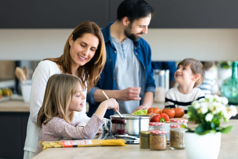 Shot of beautiful cute family having fun while cooking together in the kitchen at home.